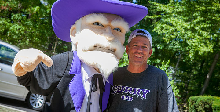 A Curry College Dad poses for a photo with the Colonel mascot