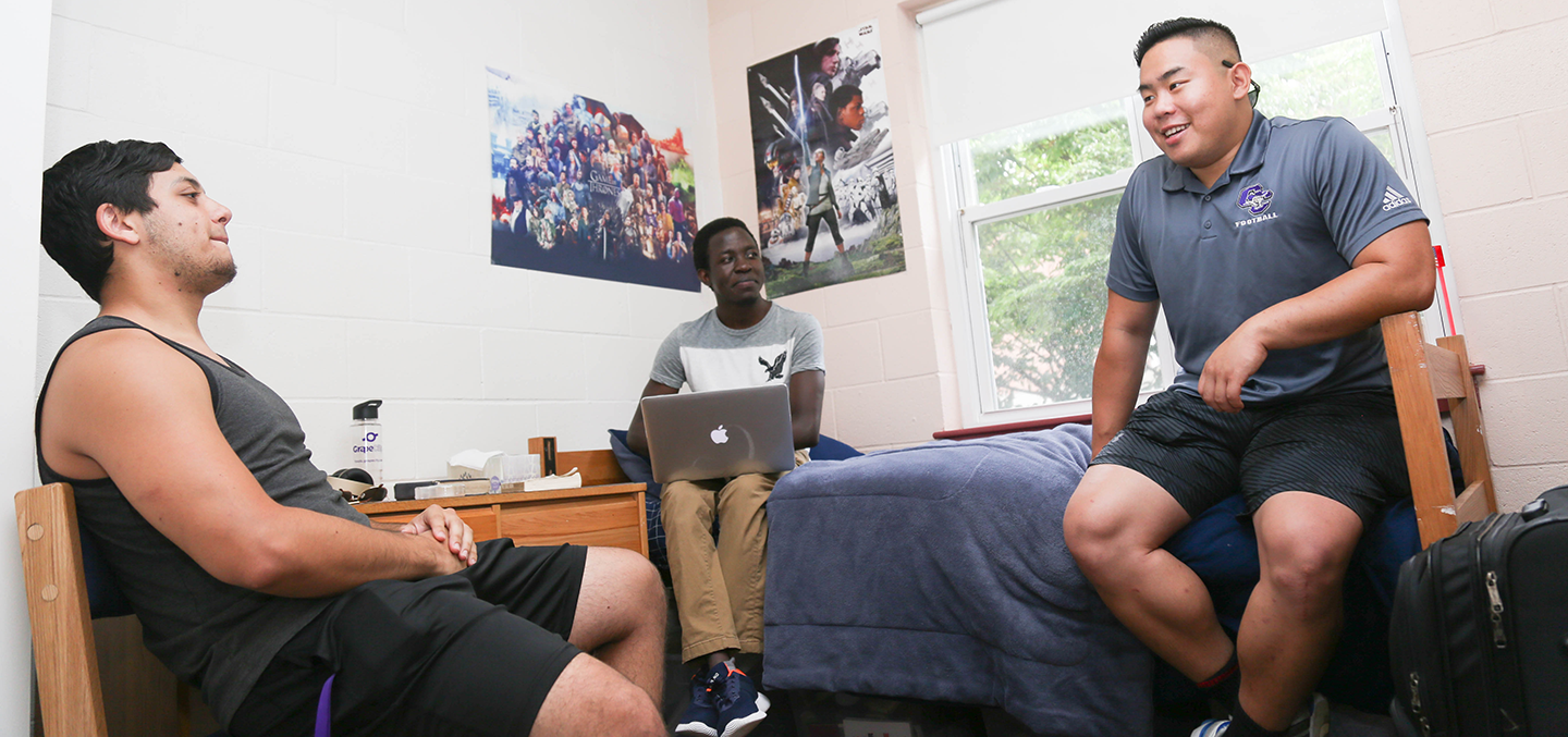 Three male students hanging out in a residence hall room