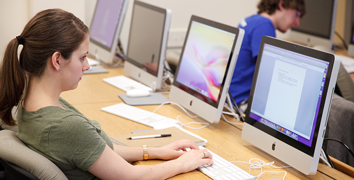 A student types on a computer in the MAC lab