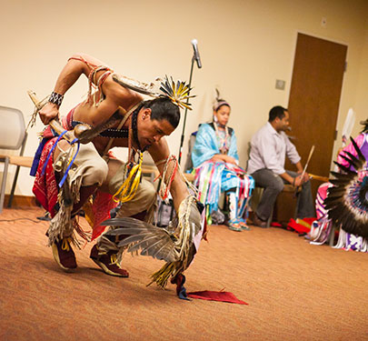 A Native American dancer performs on campus