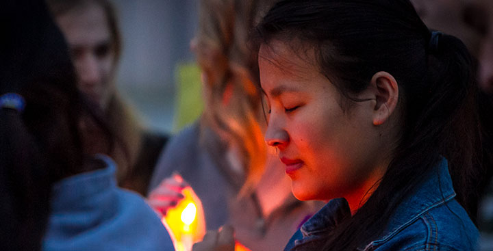 A student attends a candle light vigil