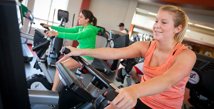 Students exercise together on bikes at the Fitness Center