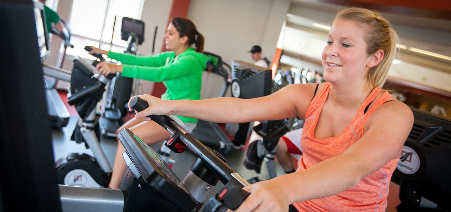 Students exercise on fitness center bikes