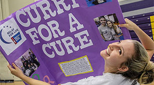 "A student holds up a ""Curry for a Cure"" sign at the Involvement Fair"