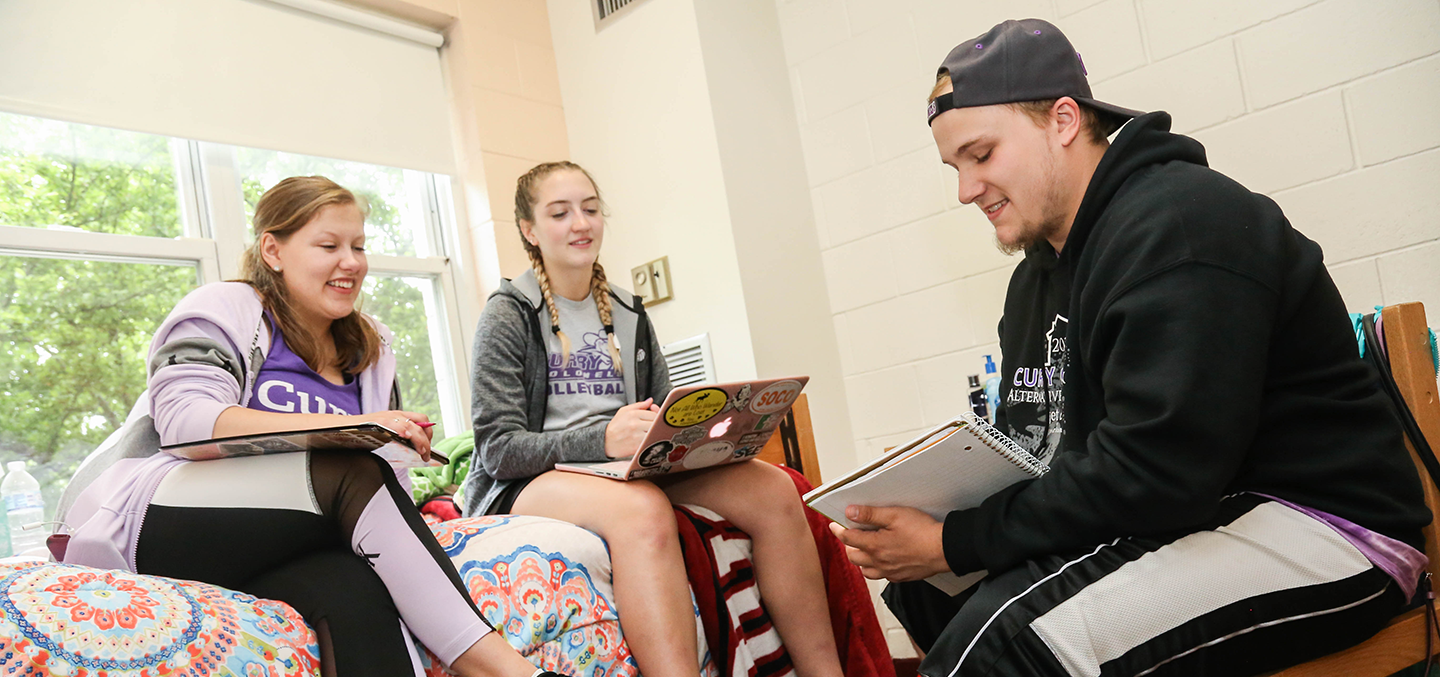 Curry students studying together in a campus residence hall