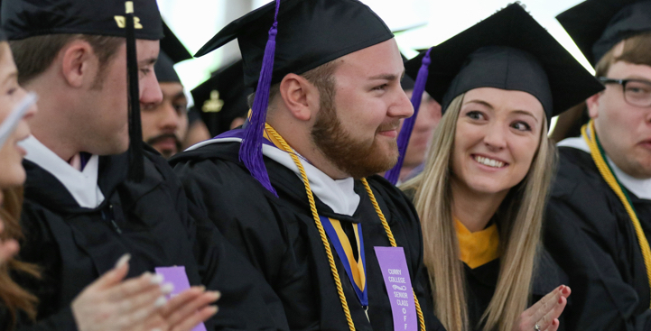 Curry College students smiling at Graduation