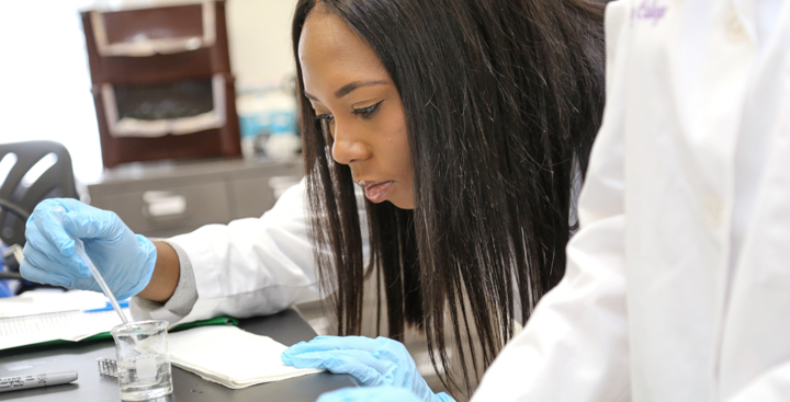 A student performs a science experiment in the Biology lab at Curry College