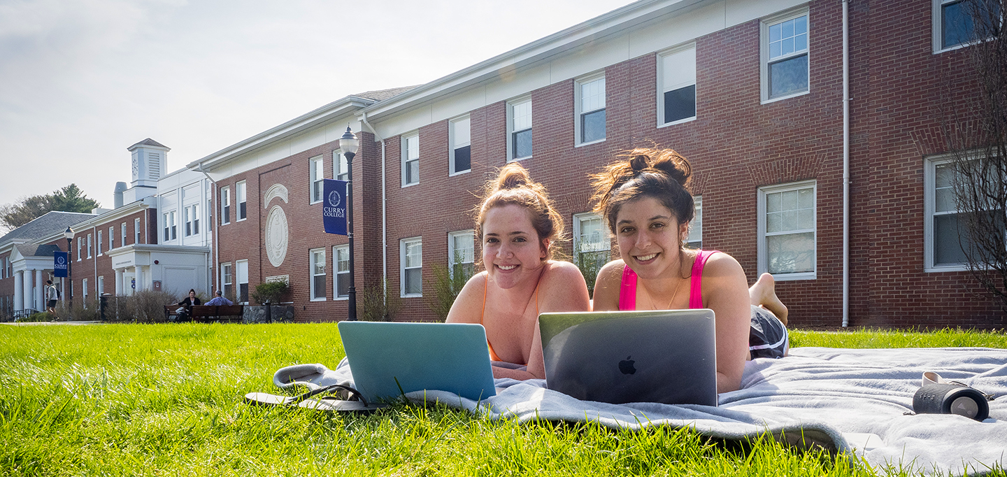 Students laying on the grass on the Curry College campus